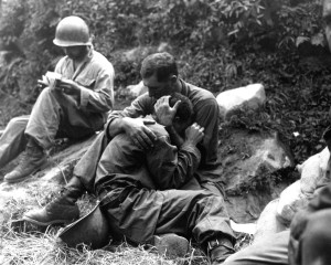 A GI comforts a grieving infantryman during the Korean War
